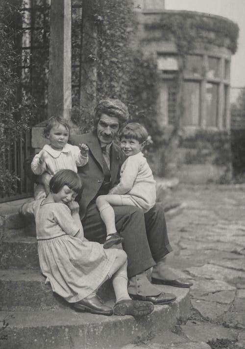 Grayscale Photo of Family Sitting on Concrete Steps