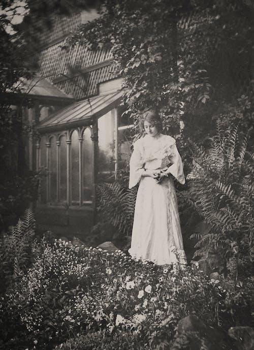 Woman in White Dress Standing on Flower Garden