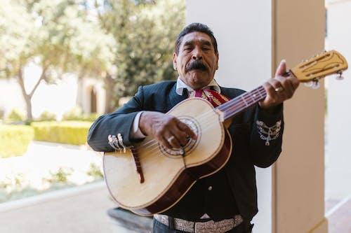 Man in Black Suit Playing Brown Acoustic Guitar