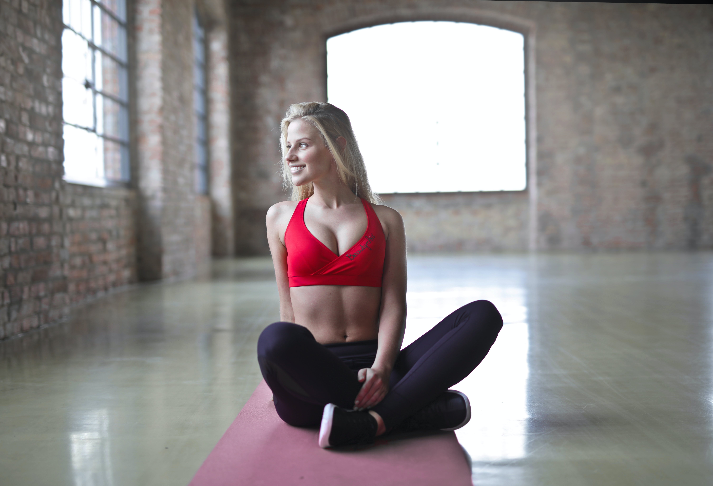 Woman Wearing Red Sports Bra Sitting on Red Yoga Mat