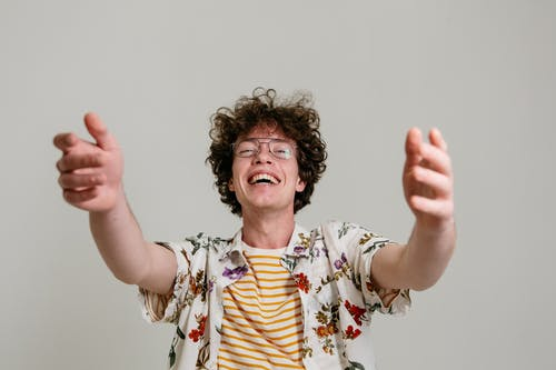 Close-Up Photo of a Man in a Floral Polo Laughing while Lifting His Hands