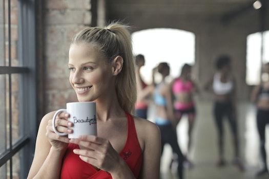 Woman Wearing Red Tank Top Holding White Ceramic Mug