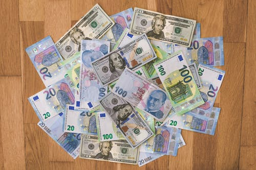 10 and 20 Banknotes on Brown Wooden Table