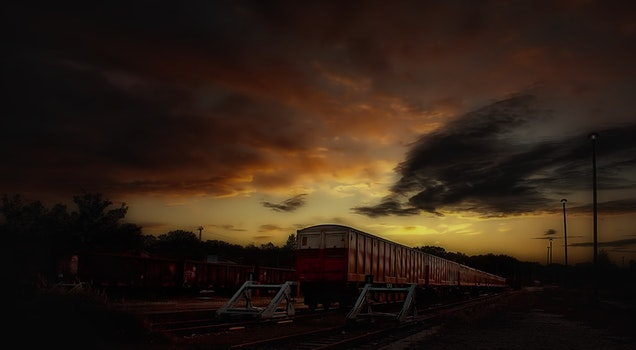 Red and White Train Taken during Sunset