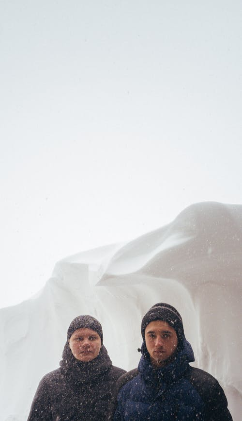 Two Men Standing on the Snow