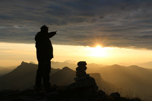 Silhouette of Man Standing on Cliff during Sunset