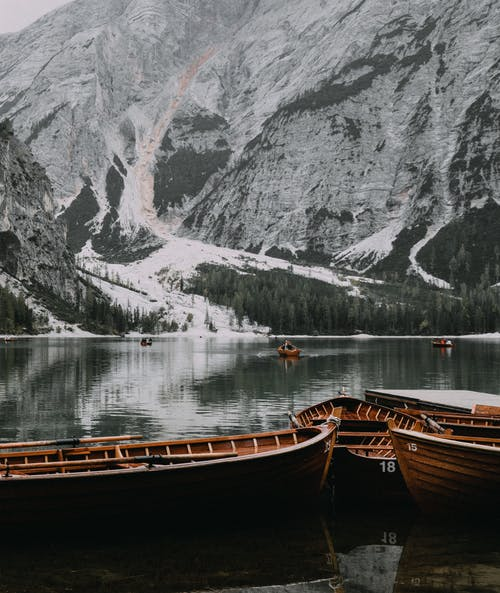 Brown Wooden Boats on Lake Near Snow Covered Mountain