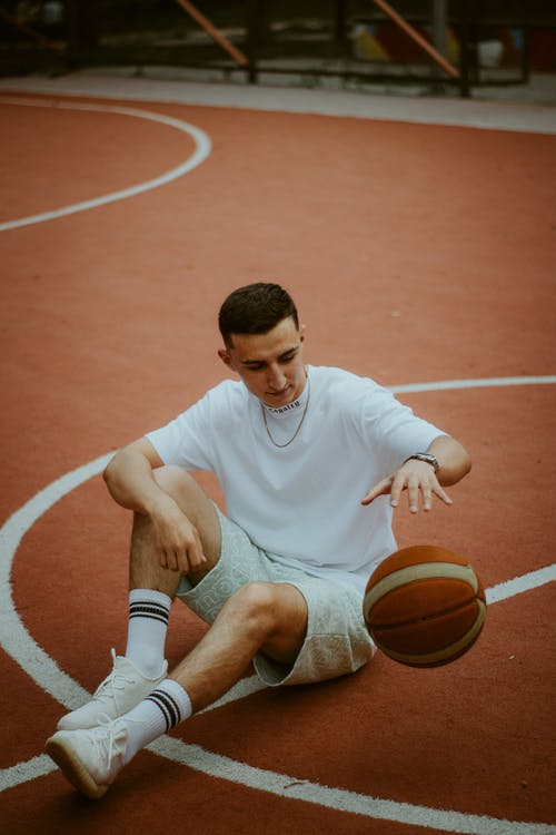 Man in White Nike Crew Neck T-shirt and Gray Shorts Sitting on Basketball Court