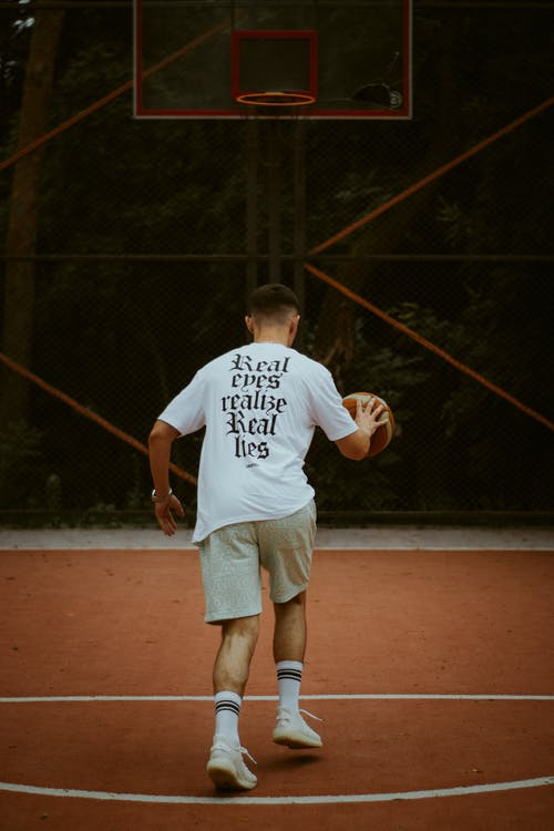 Boy in White Crew Neck T-shirt and White Shorts Running on Track Field