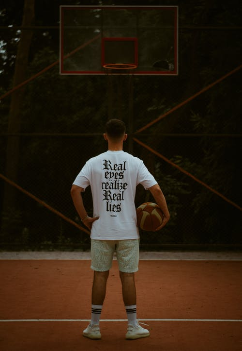 Man in White Crew Neck T-shirt Standing on Brown Wooden Floor