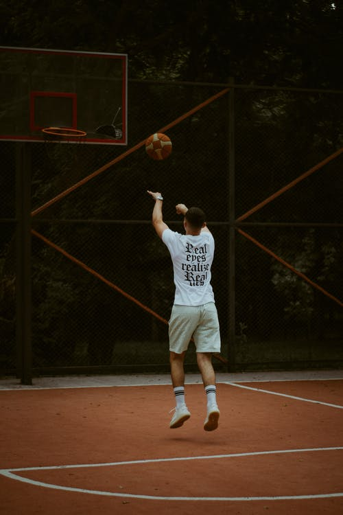 Man in White Tank Top and White Shorts Playing Basketball