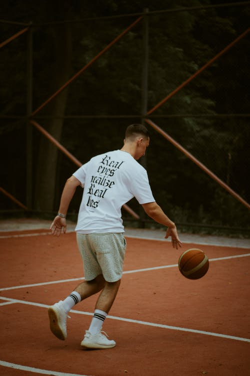 Man in White Crew Neck T-shirt and Brown Shorts Playing Basketball