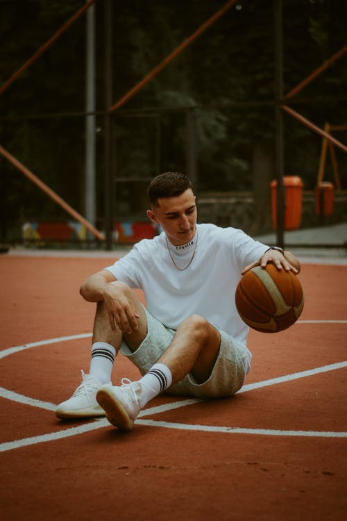 Man in White Nike Crew Neck T-shirt and Brown Shorts Sitting on Basketball Court