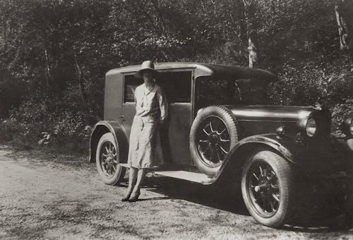 Woman in Dress Standing Beside Vintage Car Along Roadside