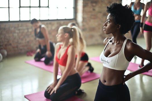 Enfoque selectivo Fotografía de mujer en blanco Sujetador de deportes de pie Cerca de mujer sentada en estera de yoga rosa