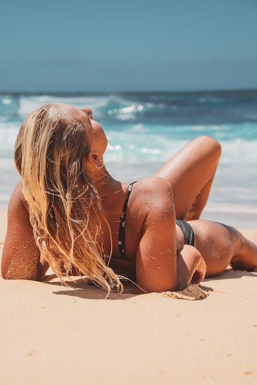 Woman in Black Bikini Lying on Beach Sand