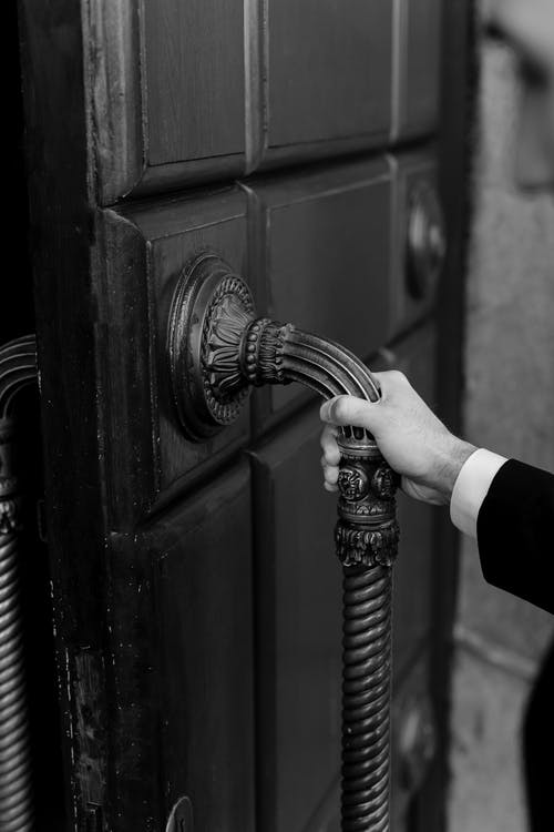 Grayscale Photo of a Person Holding a Door Handle