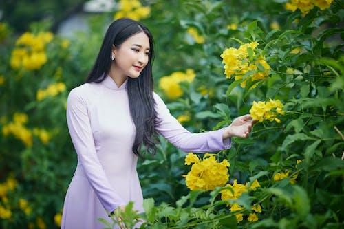 Asyalı, beyaz üst, bitki örtüsü içeren Ücretsiz stok fotoğraf