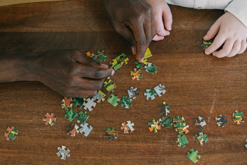 Close-Up Shot of Two People Playing Jigsaw Puzzle on a Wooden Surface