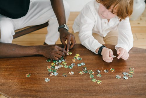 A Person Teaching a Child How to Solve A Jigsaw Puzzle