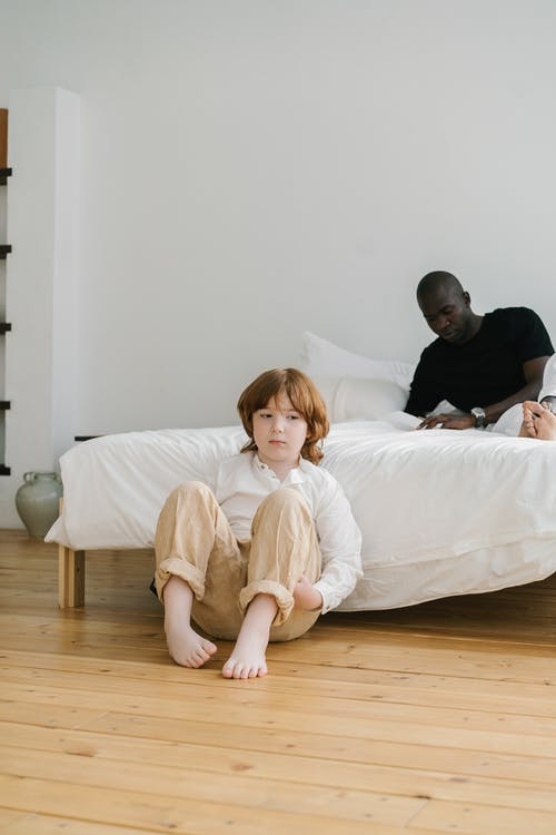 A Child Sitting on the Floor Beside a Bed With a Man Lying on Top
