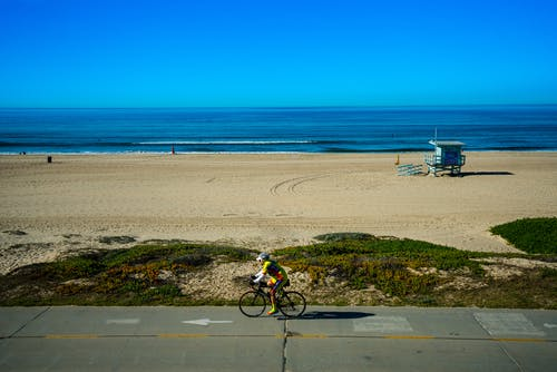 Lonely cyclist riding bike near seashore