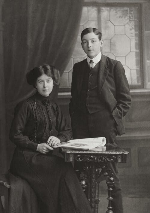 A Gentleman Standing Beside A Woman Seated By The Table