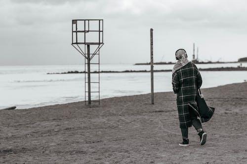 A Person Walking on a Beach