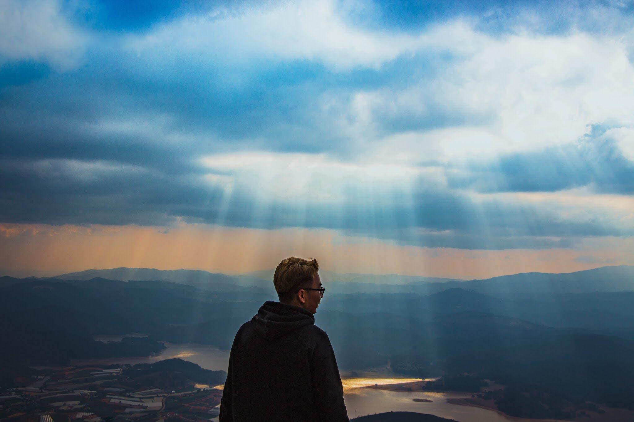 Man Wearing Black Jacket Above The Mountain