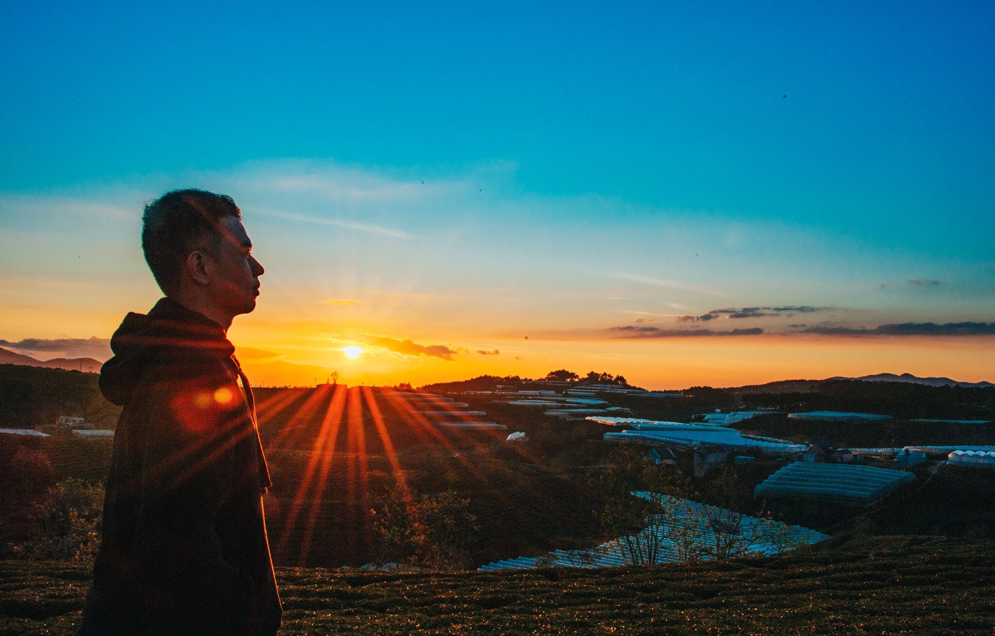 Photo of a Man Wearing Hoodie During Sunset