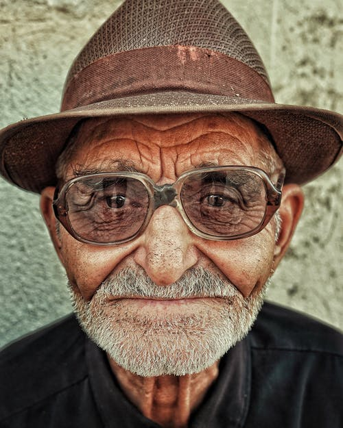 Headshot of an Elderly Man in Fedora Hat Looking at Camera