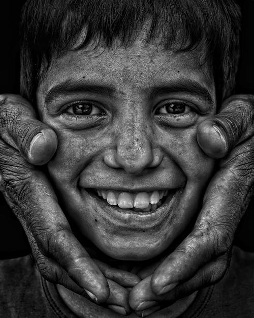 Grayscale Photo of a Smiling Child