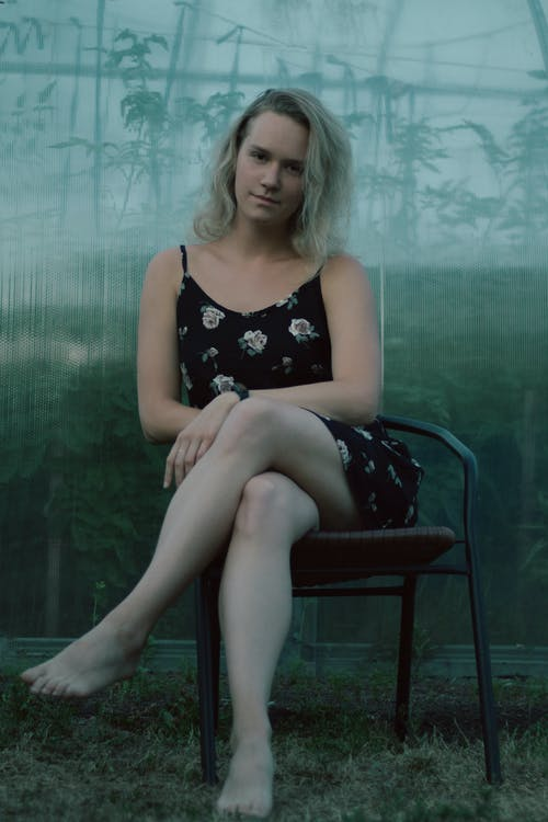 Pretty Woman in Floral Dress Sitting and Looking at Camera