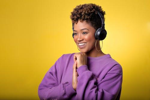 Woman in Purple Long Sleeve Shirt Wearing Black Headphones