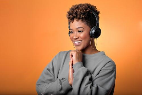 Woman in a Gray Long Sleeve Shirt Wearing Black Headphones