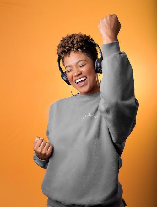 Man in Gray Sweater Wearing Black Headphones