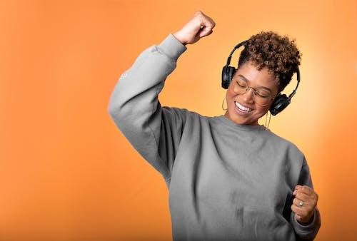 Woman in Gray Long Sleeve Shirt Dancing to Music
