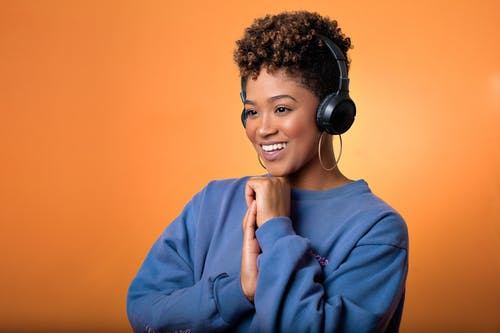 Woman in Blue Sweater Wearing Black Headphones