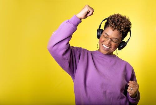 Man in Purple Sweater Wearing Black Headphones