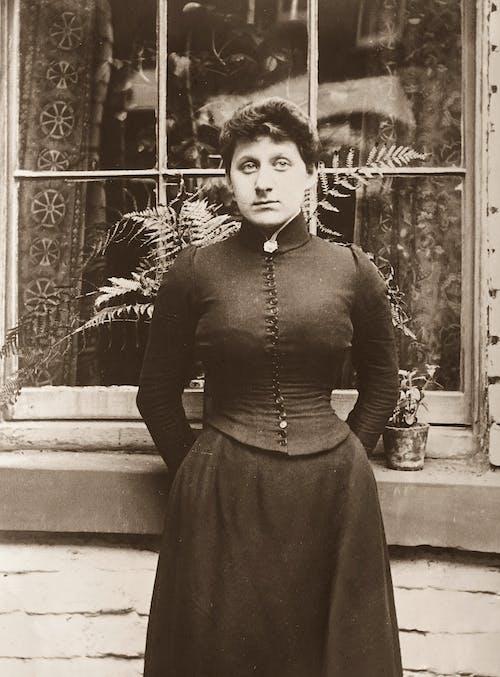 Grayscale Photo of Woman in Long Sleeve Dress Standing Near A Window
