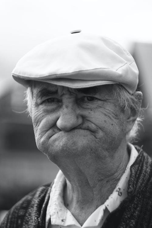 Grayscale Photo of an Elderly Man with a Hat
