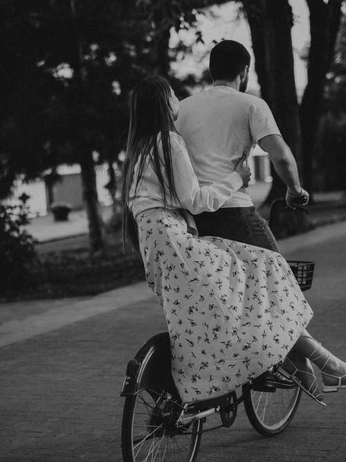 Grayscale Photo of a Couple Biking