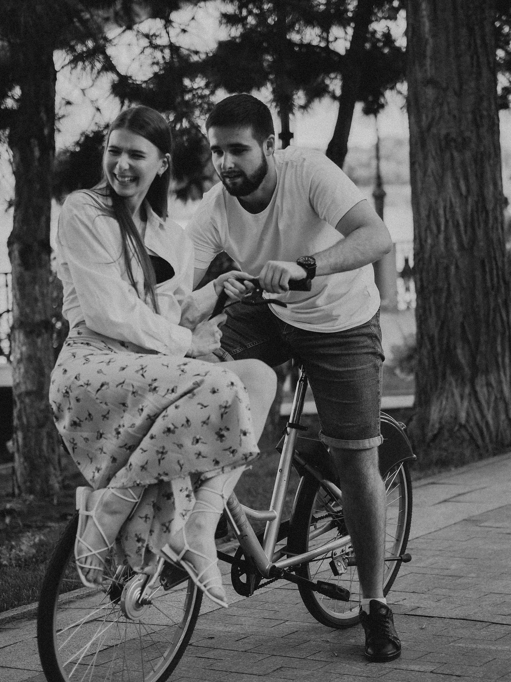 Man and Woman Riding on Bicycle in Grayscale Photography