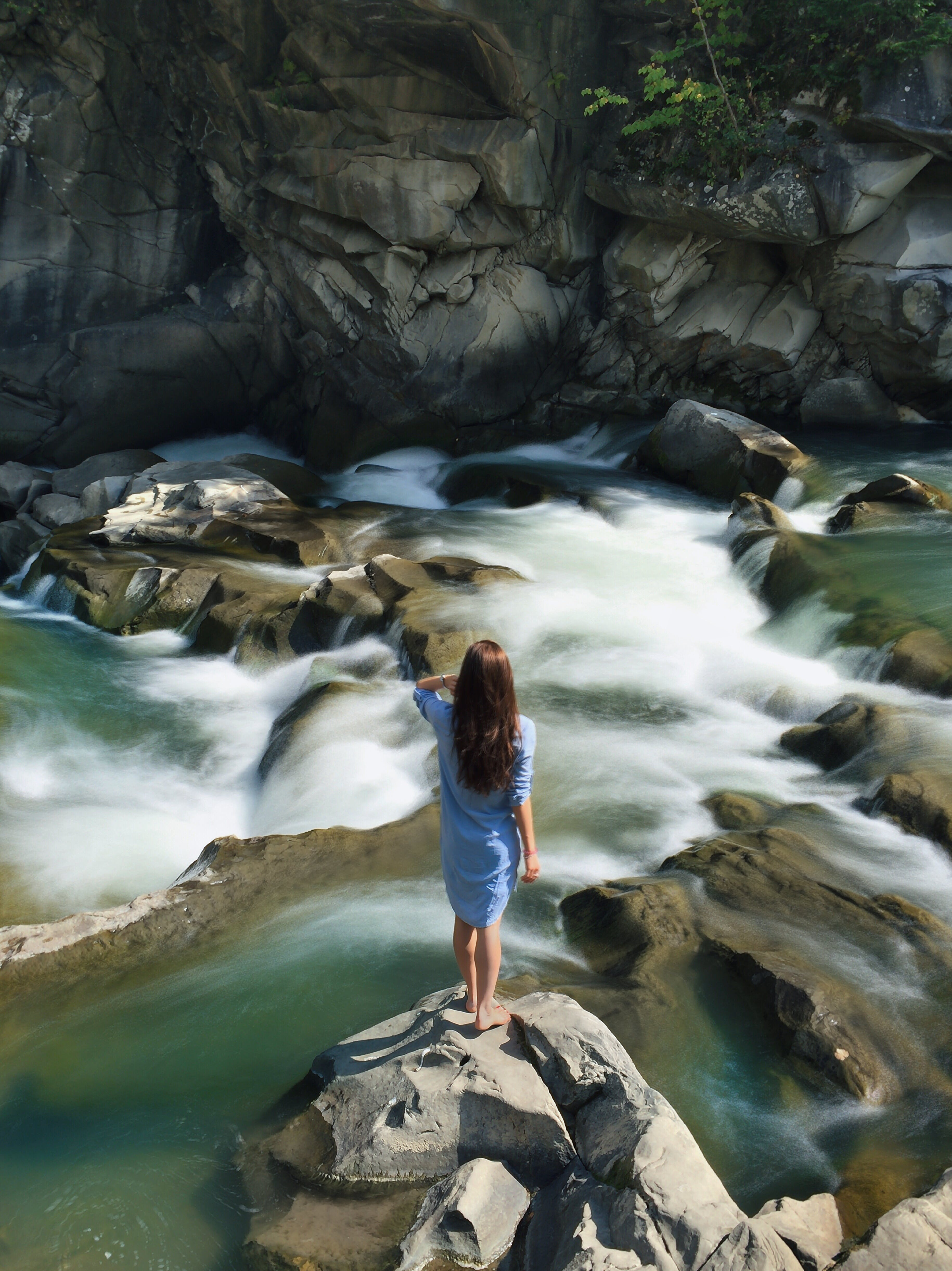 Woman in Blue Long-sleeved Dress Standing in Middle of Rock With Raging Water