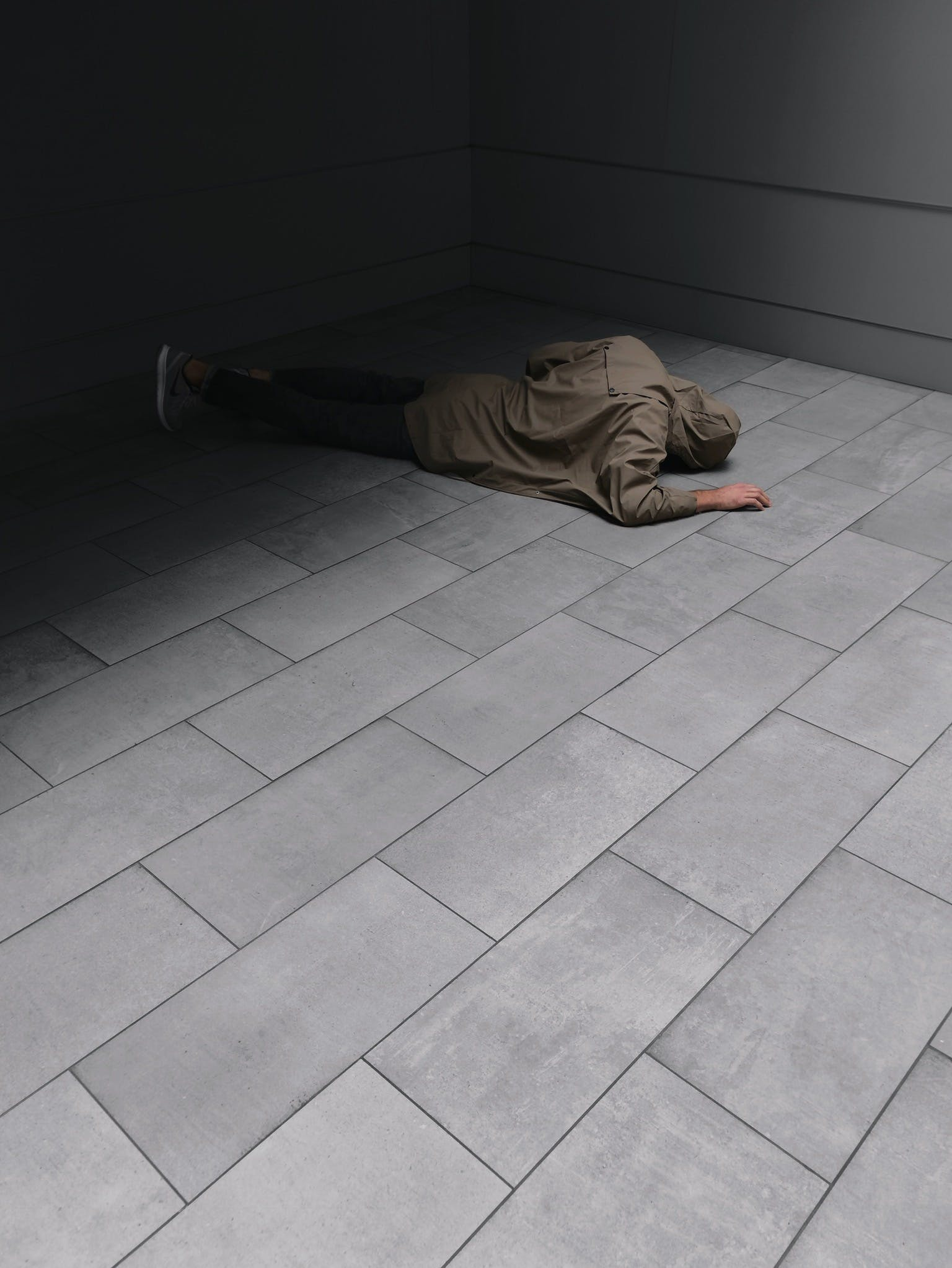 Person Wearing Grey Hoodie and Black Jeans Laying on Floor