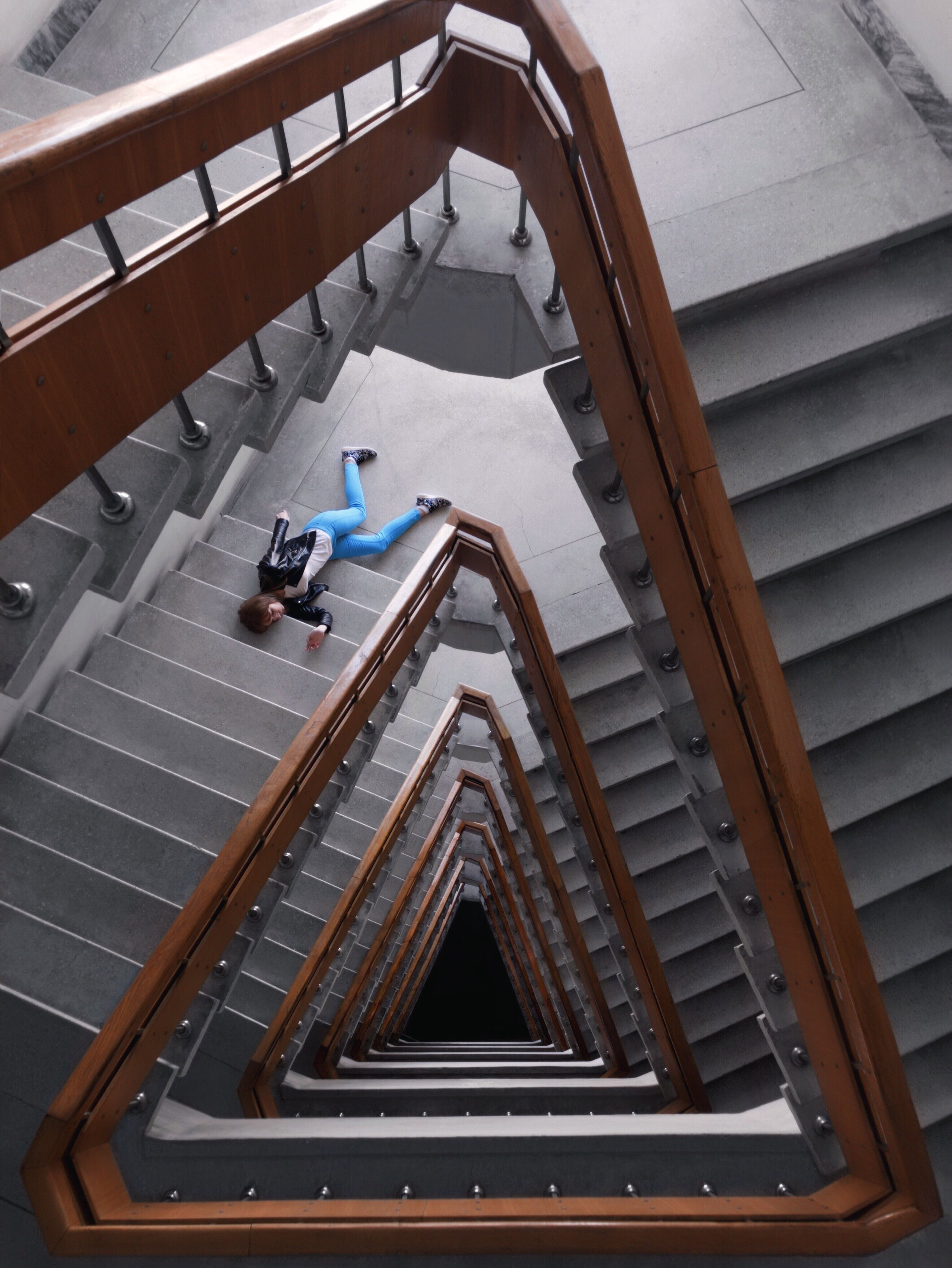 Person In Black Jacket And Blue Denim Pants Laying On Spiral Staircase