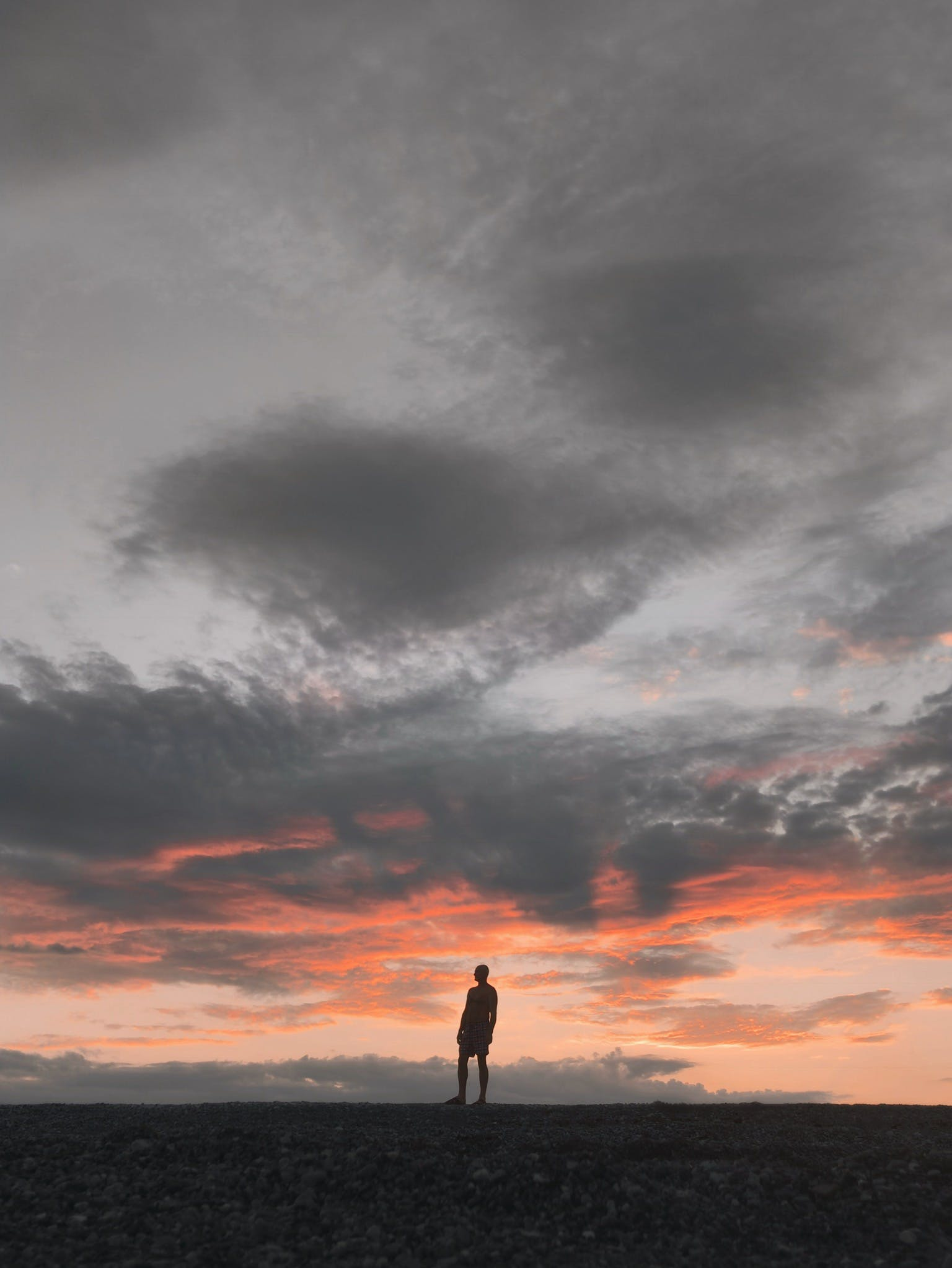 Silhouette of Man Standing Underneath Gray Sky