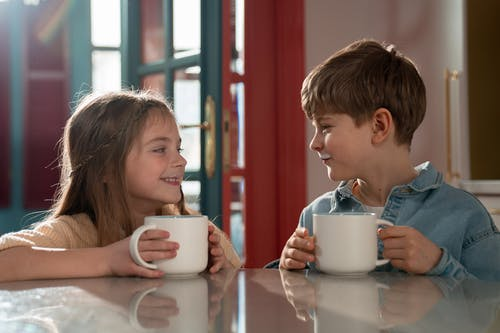 Two Kids Looking at each other While Holding Cup of Milk