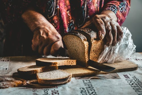 Close-Up Shot of a Person Slicing a Bread on a Wooden Chopping Board