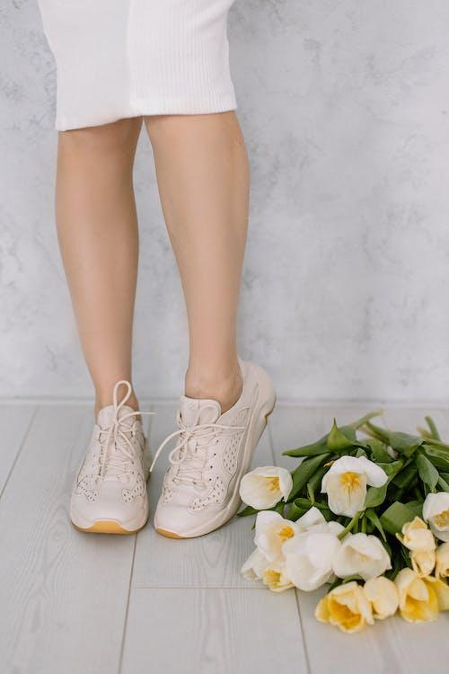 Person's Rubber Shoes Beside a Flower Bouquet